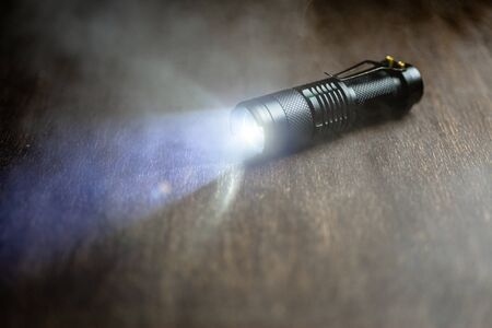 Tactical waterproof flashlight. LED flashlight shines on the table in smoke..