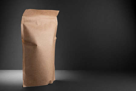 eco-friendly packaging, the package is isolated on a dark background. Copy space. Black paper background.