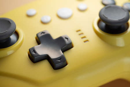 Arrow buttons of a yellow game controller close-up.