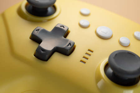 Arrow buttons of a yellow game controller close-up. Game development. Retro video games.