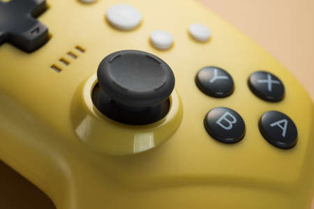 Stick of a yellow game controller close-up. Video games, entertainment at home.