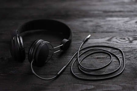 Best Headphones for Music. The headphones are dark in color against a wooden wall.
