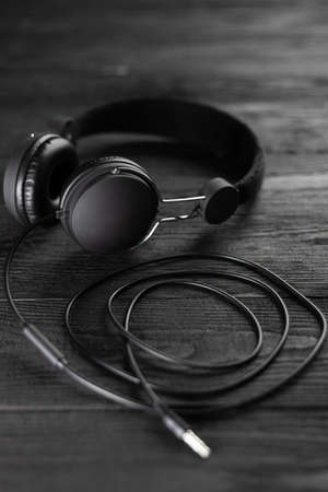 Best Headphones for Music. Headphones are dark in color against a wooden wall. Headphones for music production. Standard-Bild