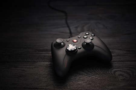 Black gamepad on a dark wooden background. Cybersport. Russia, 07/20/2020 Editorial
