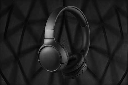 Wireless headphones on a dark background. Wireless black headphones on a futuristic background. Listen to music with headphones. High quality sound.