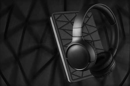Headphones and notebook on a dark background. Audio book concept.