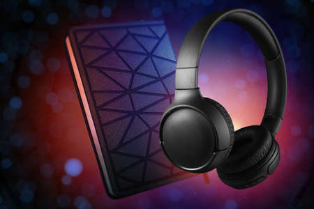 Headphones and notebook on a color light background. Audio book concept. Standard-Bild