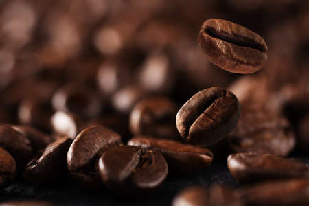 Falling roasted coffee beans background with copy space. Coffee beans in the factory. Coffee beans fall onto the table. Standard-Bild