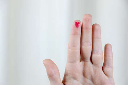 Diabetes awareness. World Diabetes Day concept. Close up of man with red heart on forefinger. . High quality photo