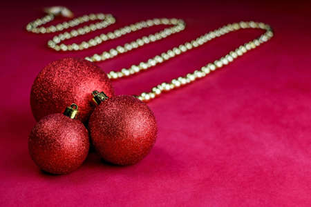 RED SHINY CHRISTMAS TREE DECORATION. A close up of a red and gold christmas tree decorations on red background. Christmas ball and Christmas decorations. High quality photo
