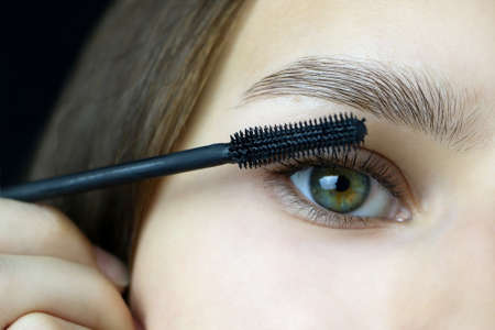 Close up of beautiful face of young woman getting make-up. a young woman applying a mascara to her eyelashes on a dark background.