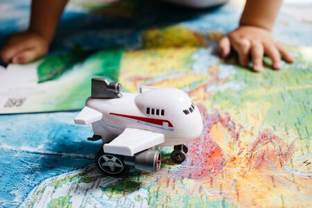 A little baby playing with an aircraft toy on the world map, childs hands, travel with children