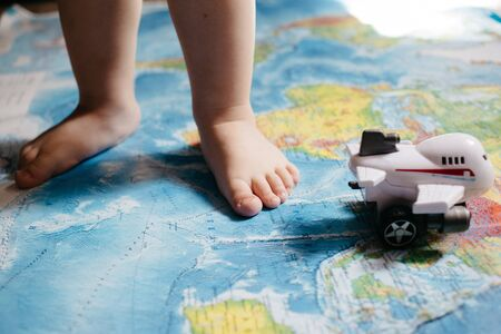 A little baby playing with an aircraft toy on the world map, close up legs, travel with children