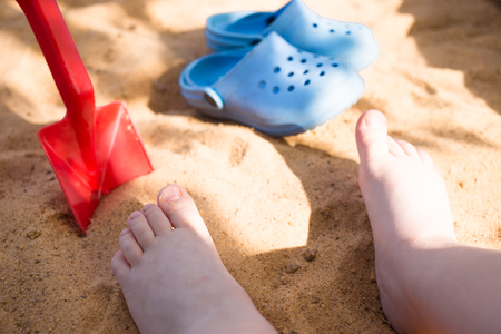the babys legs in the beach sand, blue flip flops and a toy shovel, play in the sandbox Stockfoto