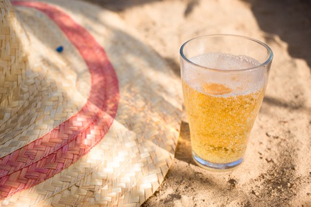 Cold beer and a summer hat on the beach. Relaxing vacation concept image