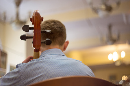 close up of a man playing the cello, a real concert, rear view