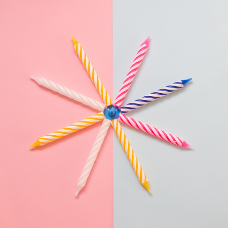 Multi-colored striped candles for birthday on the pastel colored background. Minimalism. Flat lay.