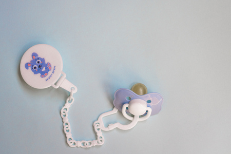 baby blue pacifier with a pin on a blue background, copy space