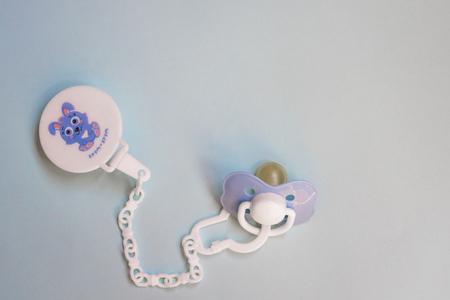 Chupete azul bebé con un alfiler sobre un fondo azul, espacio de copia