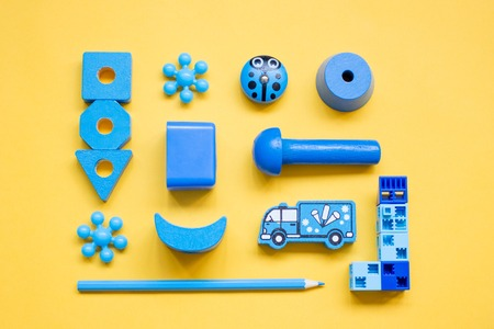 blue children's toys, laid out in a pattern on a yellow background, top view Foto de archivo