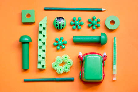 green children's toys, laid out in a pattern on a orange background, top view Фото со стока