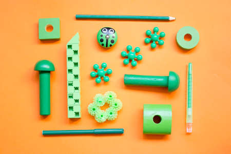 : green children's toys, laid out in a pattern on a orange background, top view