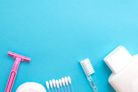 top view personal care products. white bottle, pink razor, ear sticks, cotton pads, toothbrush on blue background. copy space 免版税图像