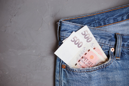 Moscow, Russia - 08 30 2018: Money financial concept. Czech crown banknotes in a pocket of blue jeans on gray background. Stock Photo