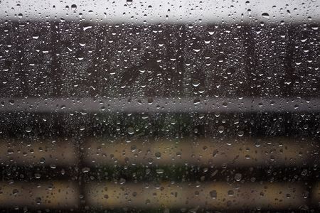 Window view blurry with heavy rain, natural raindrops on glass Stock Photo