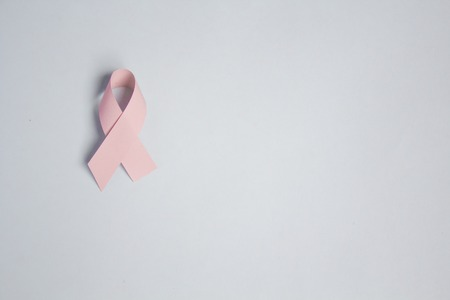 Pink ribbon symbolic bow color for Breast cancer awareness in October month on womans hand support, copy space