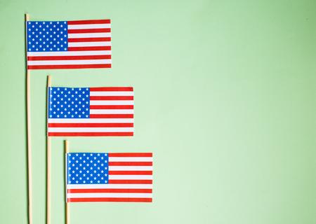 Miniature paper flag USA. American Flag on green background. Reklamní fotografie - 110793023