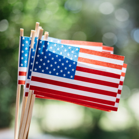 Miniature paper flags USA. American Flag on blurred background outdoors Reklamní fotografie - 110794574