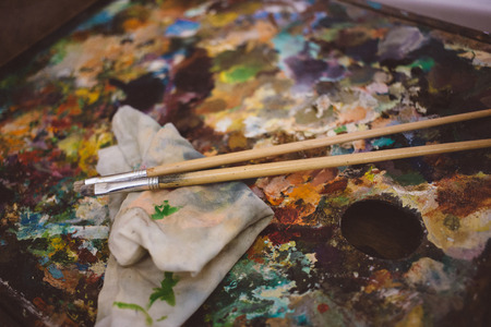 a real artists palette, oil paints and two paint brushes