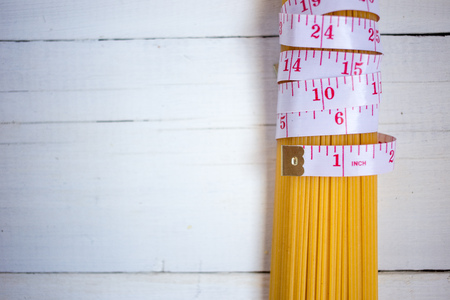 Measuring tape,diet theme. with bunch of uncooked Italian pasta spaghetti on the white wooden background. Diet, healthy food concept 写真素材
