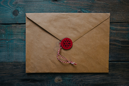 letter to Santa Claus, envelope with wooden Christmas decor in the form of wax seal, dark wooden background