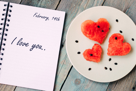 February 14th and words I love you in the notebook, watermelon in the heart shape on vintage wooden table. Archivio Fotografico