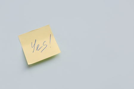 text Yes on yellow paper sticker on the blue background, Success and Goal Concept Stock Photo