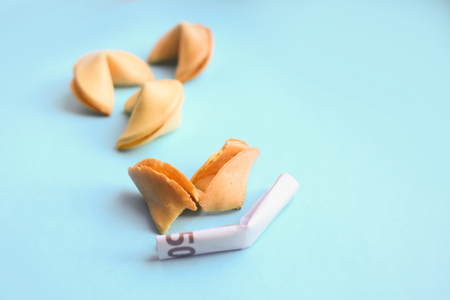 Euro banknote inside Chinese fortune cookies on blue background