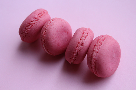 Four pink macaroons on a light pink background.