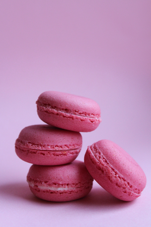 Four pink macaroons on a light pink background, minimal food concept