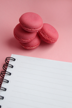 Four living coral macaroons, empty notebook on a pink background