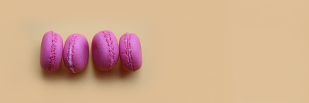 Four pink macaroons on the side on a yellow background, banner