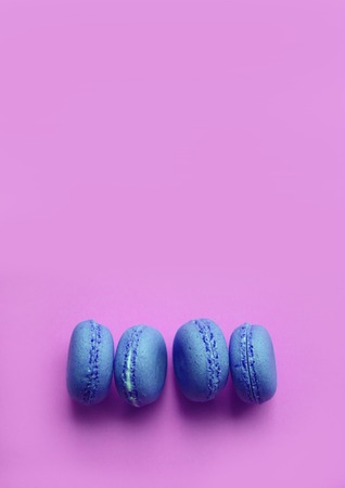 Four blue macaroons on the side on a pink background, copy space, vertical Reklamní fotografie