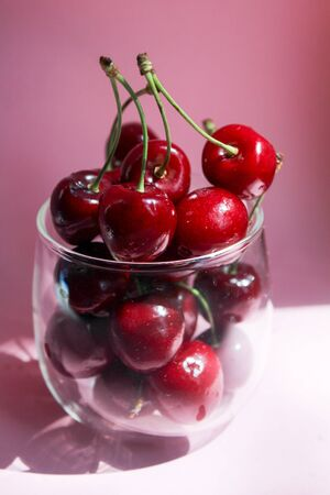 Cherries in transparent bowl, pink background. Red cherry. Fresh cherries. healthy food