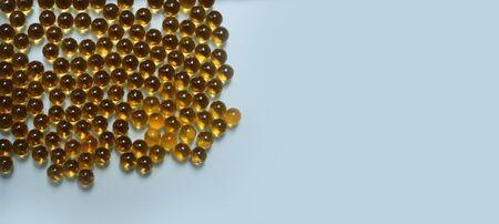 Cod liver oil omega 3 gel capsules on blue background