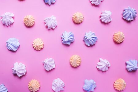 Multicolored meringue on a pink pastel background. Delicious colorful handmade dessert.