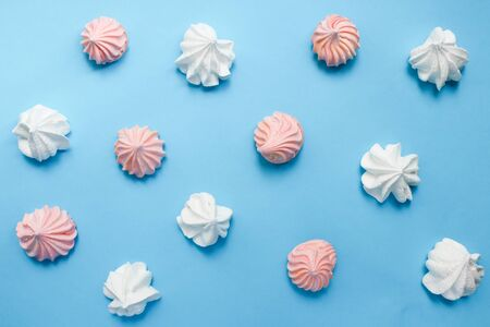 Multicolored meringue on a blue pastel background. Delicious colorful handmade dessert. Reklamní fotografie