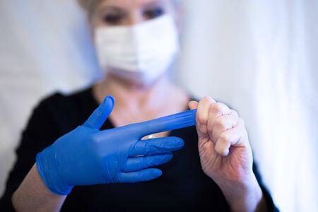 Senior woman wearing mask and removes the glove from hand. Coronavirus and epidemic virus symptoms. Фото со стока