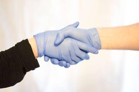 shaking hands with gloves for stop corona virus outbreak. Coronavirus and epidemic virus symptoms.
