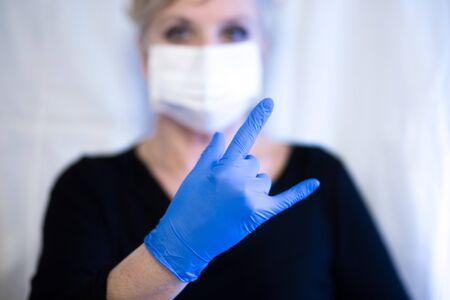 Senior woman wearing mask and wearing gloves shows the rock sign. Coronavirus and epidemic virus symptoms.